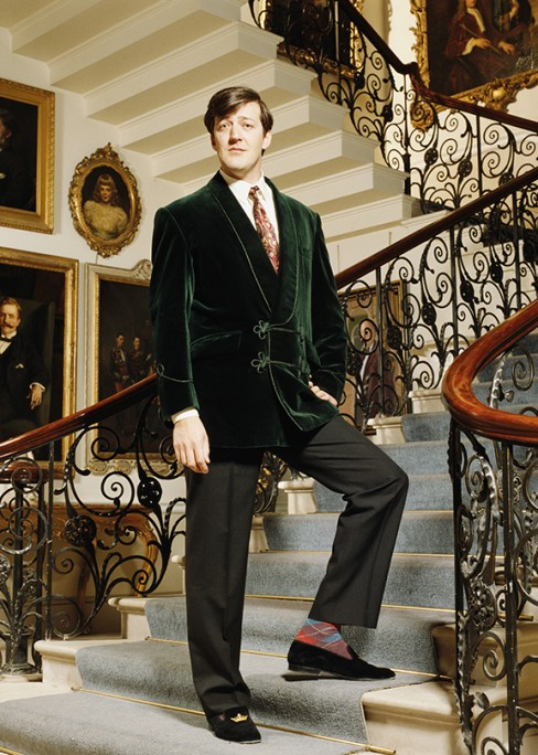 f79f25f7ef9b9 English comedian Stephen Fry looking rakish in a lounge coat and velvet  slippers.