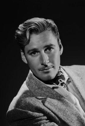 232eebb780c Errol Flynn wearing a chain printed silk cravat beneath a textured boucle  jacket
