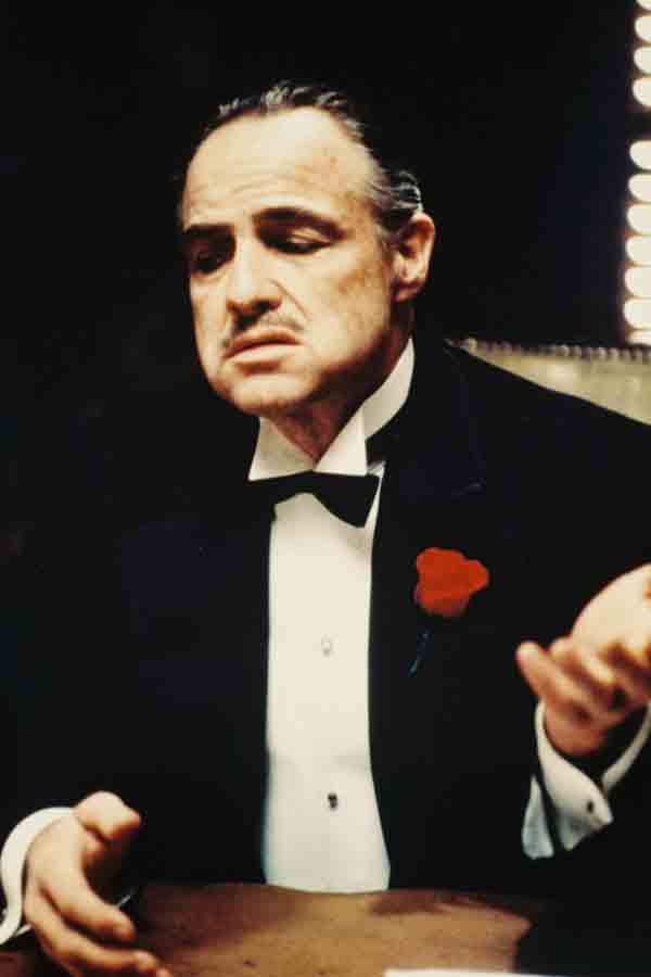 Celluloid style the godfather the rake marlon brando as don vito corleone wearing a black three piece dinner suit with silk notched lapels a white dress shirt black bow tie and a red floral thecheapjerseys Choice Image