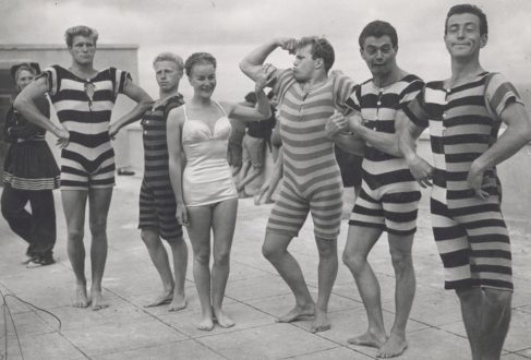 e256c8d8cb A group of men showcase striped all-in-one Victorian swimsuits, circa 1940