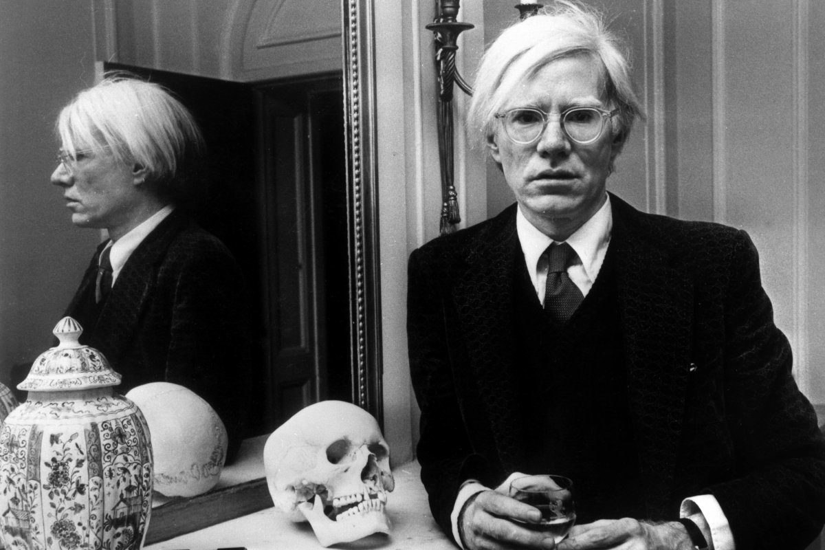 aac14a6269 The ever-eccentric Andy Warhol poses by a mirror next to a skull.